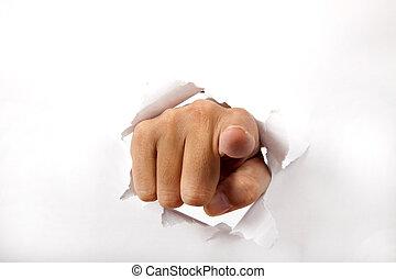 La mano atraviesa el papel blanco con el dedo apuntando hacia ti