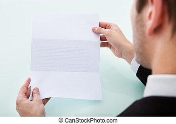 La mano de la persona sosteniendo papel en blanco