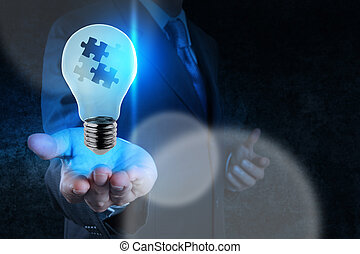 La mano de un hombre de negocios muestra una sociedad de luz y rompecabezas
