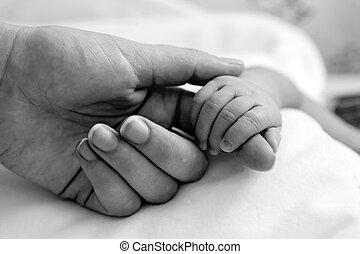 La mano del bebé sujetando el dedo de mamá