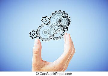 La mano del hombre muestra el mecanismo de engranajes