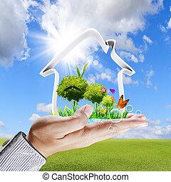 La mano humana muestra un concepto de casa verde