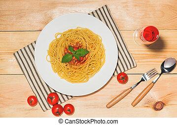 La mejor vista de los espaguetis con salsa de tomate y carne en la mesa de madera.