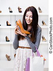 La mitad del largo retrato de la mujer guardando zapatos de tacón