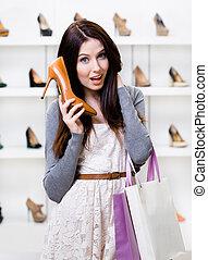 La mitad del retrato de la mujer que entrega zapatos