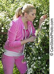 La mujer con un traje rosa en los arbustos en flor