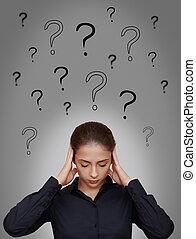 La mujer de negocios piensa mucho con muchas preguntas sobre el fondo gris