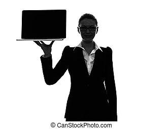 La mujer de negocios que sostiene mostrando silueta portátil