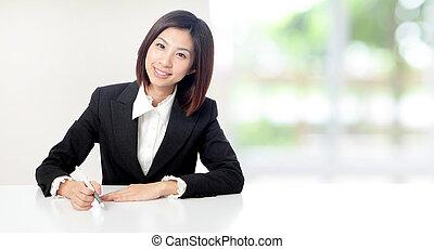 La mujer de negocios sonríe trabajando en la oficina