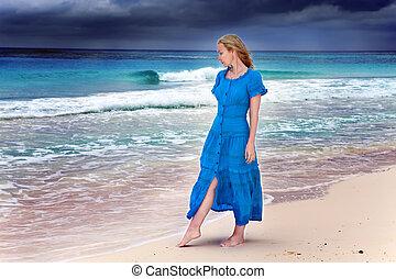 La mujer de un largo vestido azul va a la costa del mar