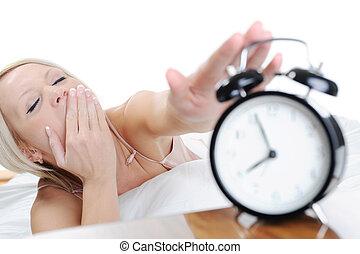 La mujer dormida apaga la alarma