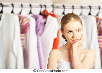 La mujer elige ropa en el armario de la casa