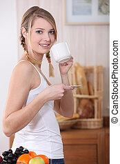 La mujer estaba en la cocina sosteniendo taza y platillo