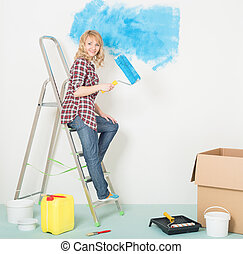 La mujer feliz hace reparaciones en casa