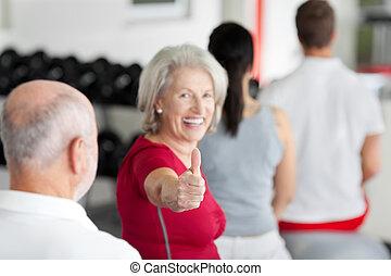 La mujer gestando los pulgares hacia arriba con la familia sentada en el gimnasio