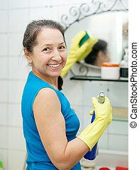 La mujer madura limpia espejos en el baño