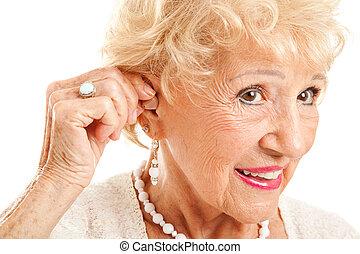 La mujer mayor inserta audífonos