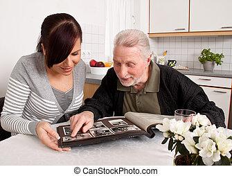 La mujer mira un álbum de fotos con ancianos