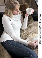 La mujer se relaja en el sofá con taza de café