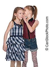 La niña le susurra algo a su amiga