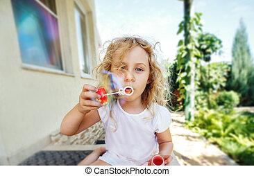 La niña linda está haciendo burbujas de jabón.