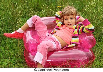 La niña se sienta a hablar por teléfono de juguete en un sillón inflable en el césped
