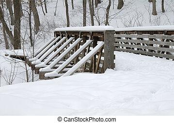 La nieve cubrió el puente de madera