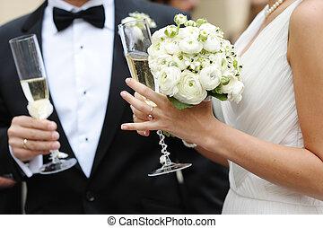 La novia y el novio sosteniendo copas de champán