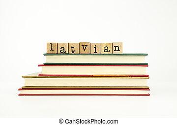 La palabra en idioma letón sobre sellos de madera y libros