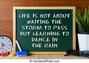 "La palabra ""vida"" no se trata de esperar a que pase la tormenta sino de aprender a bailar en la lluvia escrita en la pizarra verde sobre la mesa de madera."