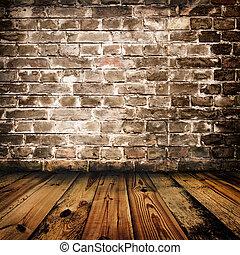 La pared de ladrillos y el piso de madera