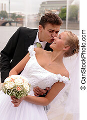La pareja de bodas en el amor besándose