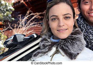 La pareja de esquiar estaba frente a una cabaña de madera