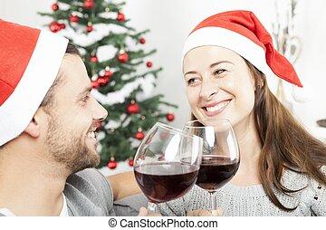 La pareja disfruta de las Navidades con vino en el sofá