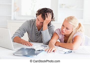 La pareja gastada haciendo sus cuentas