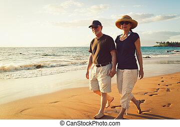 La pareja mayor disfrutando del atardecer en la playa