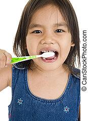 La pequeña asiática cepillándose los dientes