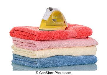 La pila de toallas de Terry y el dispositivo para planchar aislado en blanco
