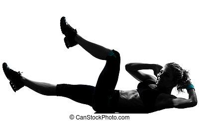 La postura femenina de ejercicio abdominal empuja hacia arriba