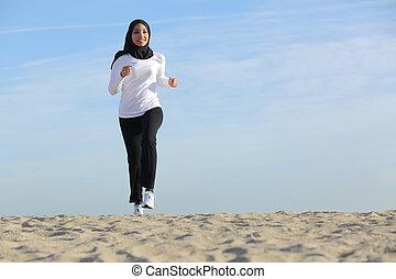La primera vista de una mujer saudita árabe que corre por la playa