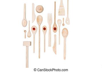 La primera vista de varios utensilios de cocina de madera con tomates de cereza aislados en blanco