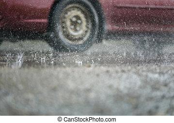 La rueda de un coche atraviesa un charco bajo la lluvia