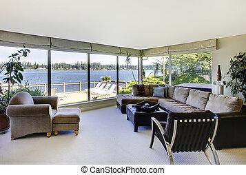 La sala de estar con chimenea y una vista de agua con ventanas grandes.