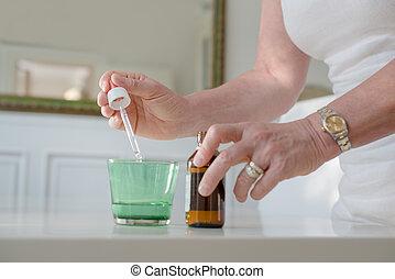 La salud y la gente, la mujer madura con medicinas y agua recetadas. Vista cerrada