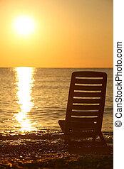 La silla vacía está de lado en la costa del mar por la noche durante el atardecer