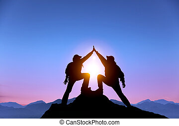 La Silueta de dos hombres con un gesto de éxito en la cima de la montaña