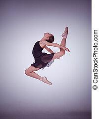 La silueta de la joven bailarina de ballet saltando en un fondo lila.