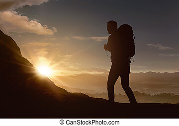 La silueta de un mochilero escalando la montaña