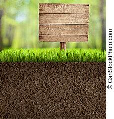 La tierra cortada en el jardín con una señal de madera