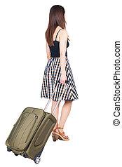 La vista atrás de una mujer andante con una maleta verde.
